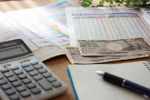 保険申込書、電卓、お金、ペン