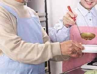介護士と料理を作る高齢者