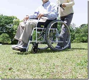 車椅子の高齢者と介助する介護士