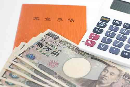 年金手帳と電卓と紙幣
