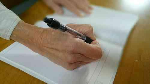 ノートに書きものをする老人の手
