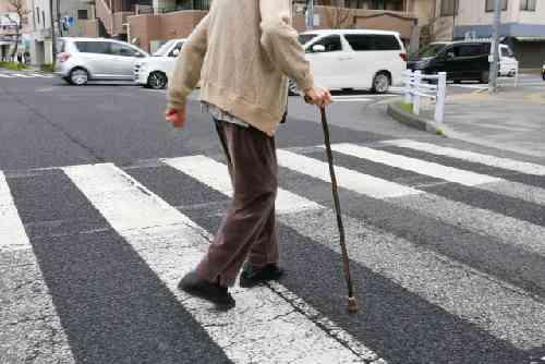 杖をついて横断歩道を渡る高齢者