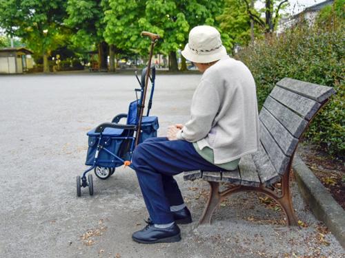ベンチで休む高齢者