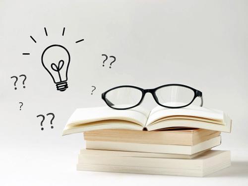 本の上の眼鏡とひらめきの電球