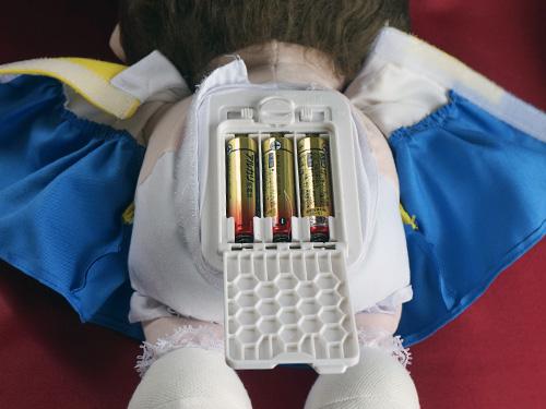 しゃべる人形のんちゃんに電池を入れているところ