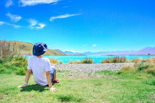 草原に座り海を眺めている女性