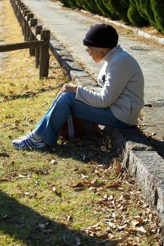 道に一人座る高齢者