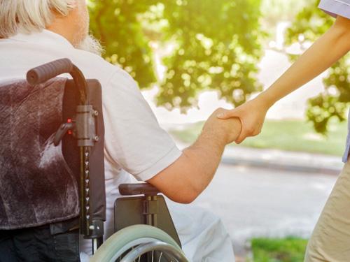 車いすの高齢者と手をつなぐ介護者