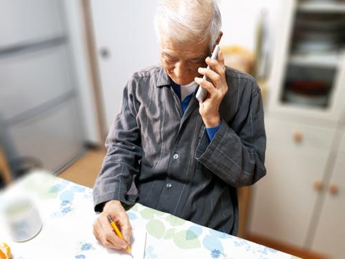 電話をしながらメモをとる高齢者